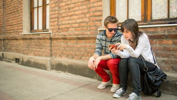 Shutterstock 135802760 - Young urban couple sharing information in the city  © Pablo Rogat