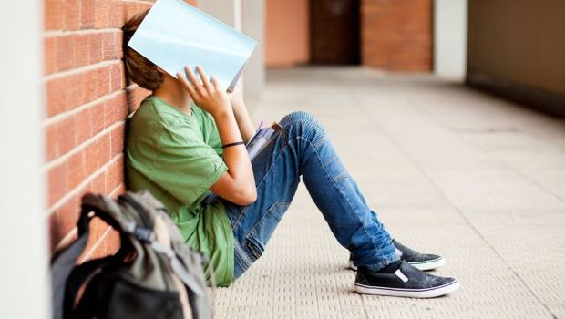 shutterstock 102482045 tired high school student using book cover his face © michaeljung